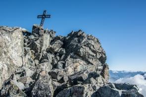 La croce di vetta spunta dalle rocce, nell'ultimo tratto antecedente la parte più complessa della cresta